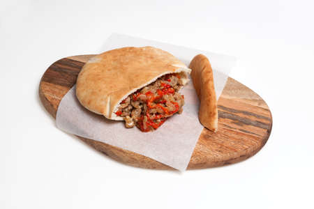 Pita or Arabic bread, stuffed with chicken and vegetables on wooden cutting board. Close-up, selective focus, copy space.