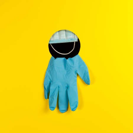 Medical face mask and disposable gloves through a hole on a yellow background with copy space. Concept - new wave of the Covid-19 coronavirus epidemic. Glove-mask mode. Personal protective equipment.