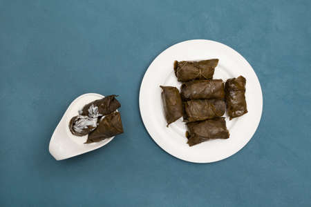 Delicious stuffed grape leaves (traditional doom Mediterranean cuisine Dolma) on white plate with sauce. Top view. Blue background with copy space.