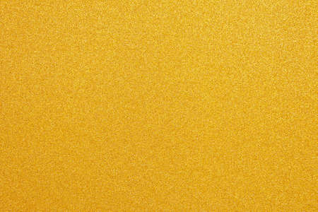 Shiny yellow leaf. Gold glitter texture. Christmas abstract background, defocused.