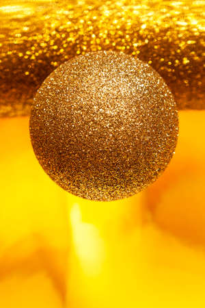Sparkling golden ball on blurred yellow background, bokeh. Close-up, selective focus.