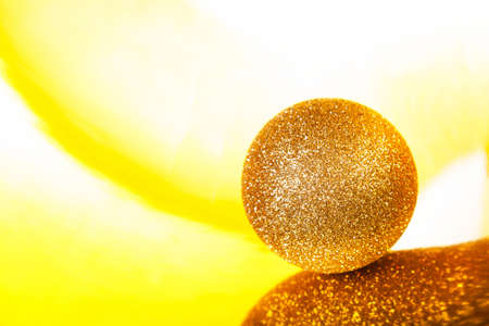 Sparkling golden christmas ball on abstract yellow background, defocused. New year's composition. Standard-Bild