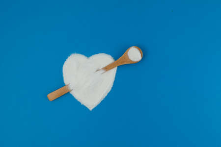 Collagen powder or protein on blue background. Healthy food supplement. Powder poured in shape of heart with spoon imitating an arrow.