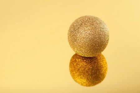 Sparkling golden christmas ball on golden mirror background, selective focus. New year composition. Standard-Bild
