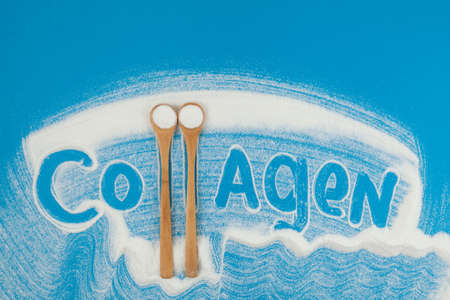 Collagen powder is scattered on a blue paper background. Beautiful lettering Collagen. Two bamboo spoon with hydrolyzed food additive. Standard-Bild