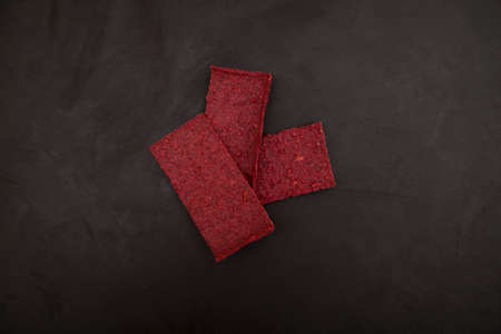 Beetroot chips on dark background. Healthy snack. Thin vegetable crispbread on rye sourdough. It can be used as base for vegan sandwiches or added to salad.