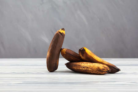 Overripe bananas on light wooden table. Gray background, selective focus, copy space. Fermented fruit is suitable for baking tasty vegan banana bread.
