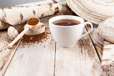 Mug of chaga tea on wooden table in a rustic style. Nearby are lied natural Chaga birch mushrooms. Healthy beverage is used in alternative medicine.