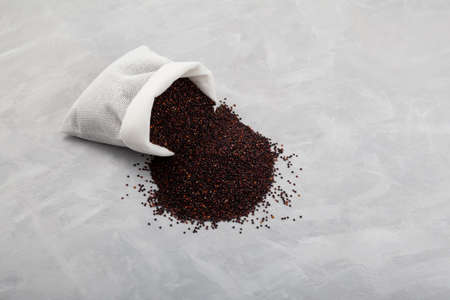 Peruvian black quinoa seeds are spilled out of the bag. Close-up, copy space. Cereals contain a large amount of protein, antioxidants, dietary fiber, vitamins and minerals. Stock Photo