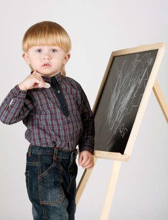 little boy draws on blackboard Stock Photo - 12163250