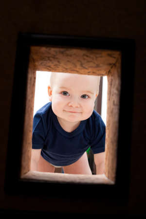 Little child looks to hole in the wall photo