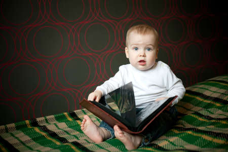 little boy reading book at home photo