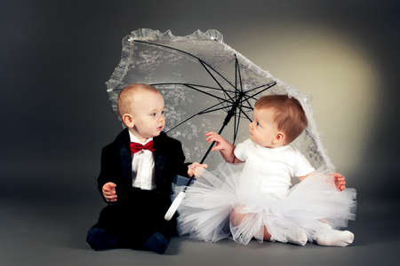 little boy and girl sitting under umbrella Stock Photo