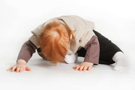 biracial: small boy laying on a white floor