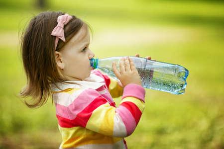 어린 소녀가 미네랄 워터를 마신다.