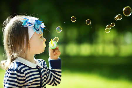 little funny girl plays with bubbles photo