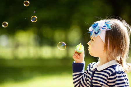 blowing bubbles: little girl plays with bubbles