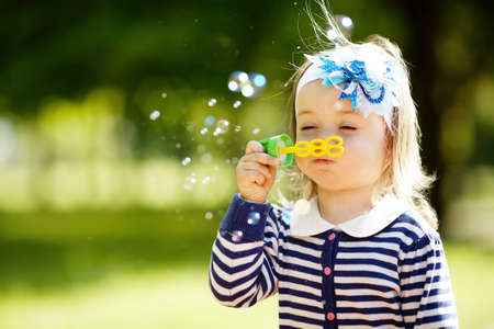 little girl plays with bubbles photo