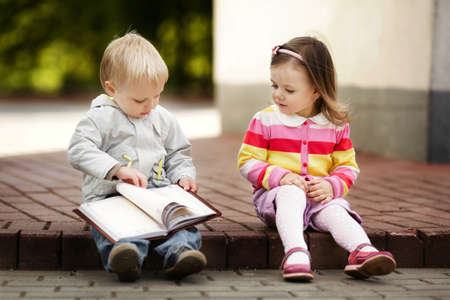 boy and girl reading book photo