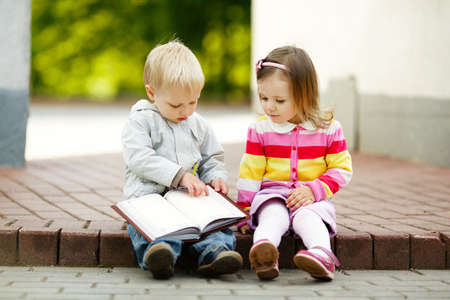 kid reading: cute boy and girl reading a book