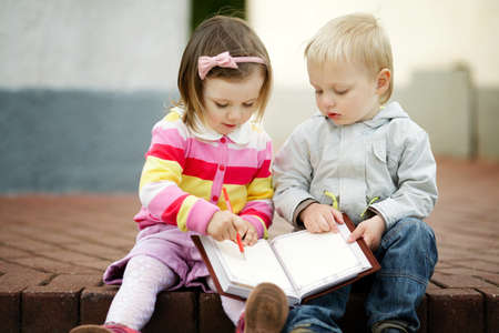 boy and girl writing to notebook photo