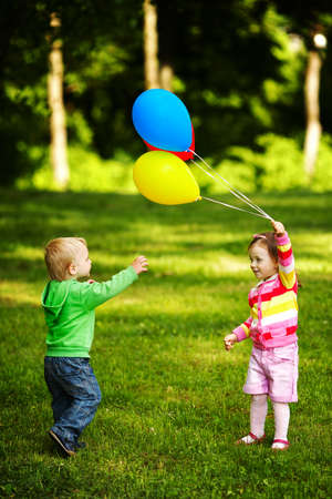 girl and boy playing with balloons in park photo