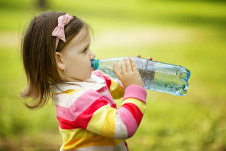 green water: little girl drinks mineral water