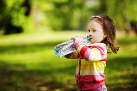 bottle with water: little girl drinks mineral water