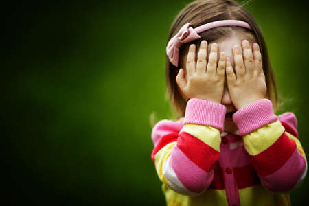 děti: holčička hraje hide-a-hledat skrývá tvář