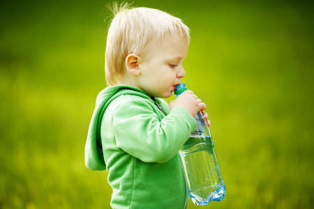 little boy drinks mineral water photo