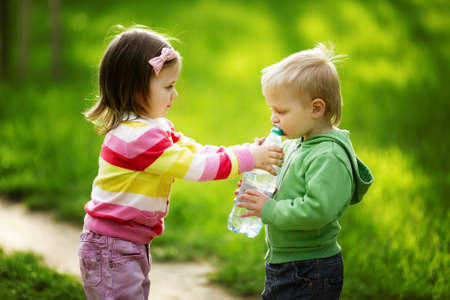 boy and girl sharing bottle of water Stock Photo