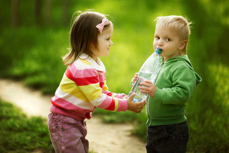 friendship: boy and girl sharing bottle of water Stock Photo