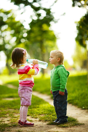sunny cold days: little funny boy and girl drinking mineral water in park Stock Photo