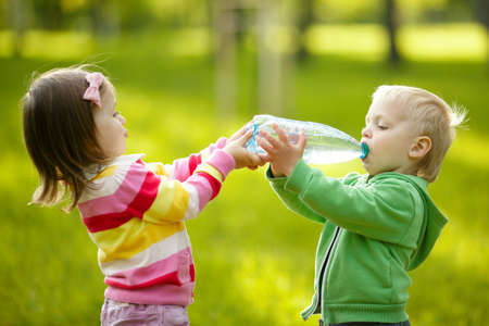 Girl helps the boy to keep a bottle