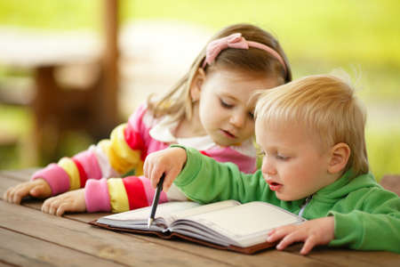 cute boy and girl reading a book photo