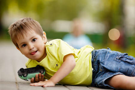 little boy plays with toy car photo