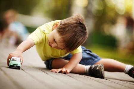 kleine jongen speelt met speelgoed auto