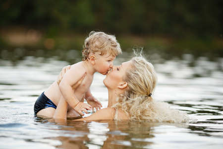 beautiful lake: beautiful young mother with her son in water