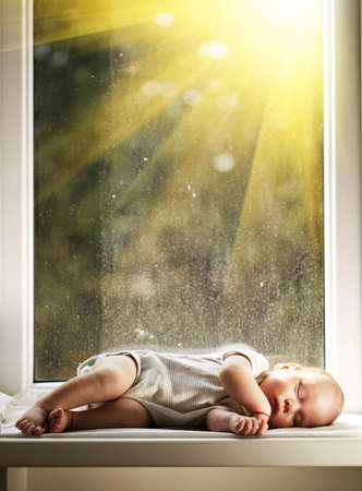 baby sleeping on white blanket on window photo