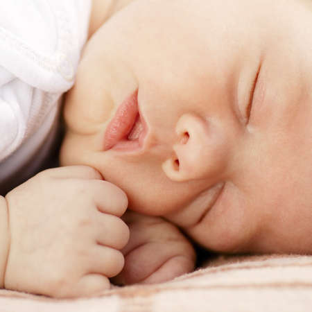close-up portrait of a sleeping baby on white photo