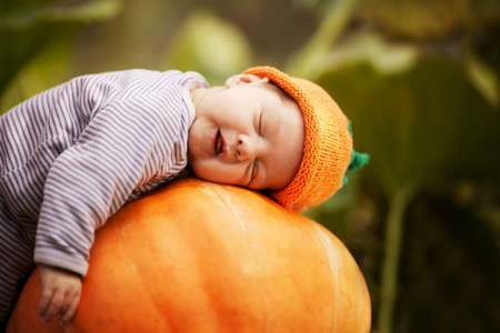 baby sleeping on big pumpkin photo