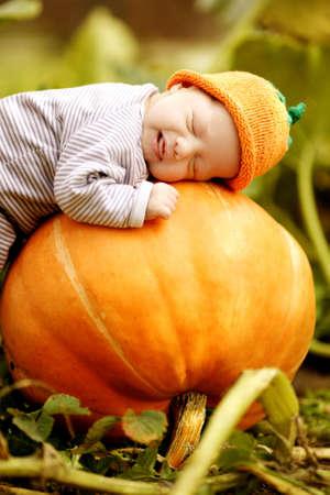 enfant qui dort: bébé qui dort sur grosse citrouille