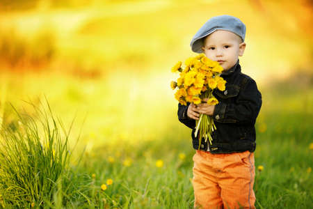 cute little boy with dandelions Фото со стока