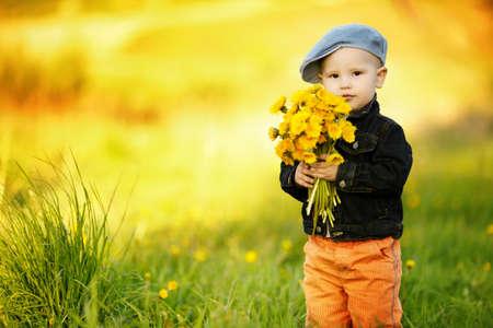 schattige kleine jongen met paardebloemen