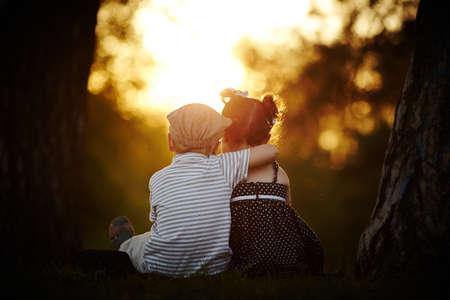 niño y niña: niño y niña en la puesta del sol