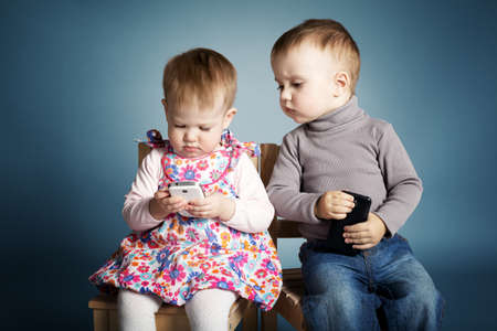 little boy and girl playing with mobile phones Stock Photo