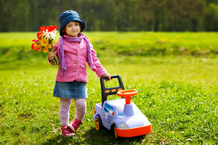 little girl with toy car and flowers photo
