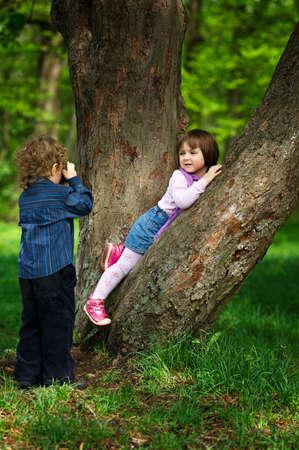 niño pequeño fotografiar chica en el parque en árbol