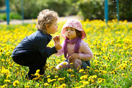 boy and girl in summer flowers field photo