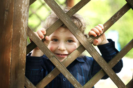 little funny boy behind the fence photo